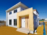国分建設の施工事例:白を基調としたキューブ状のかわいらしい家。木のぬくもりを感じる玄関は施主のこだわりポイント